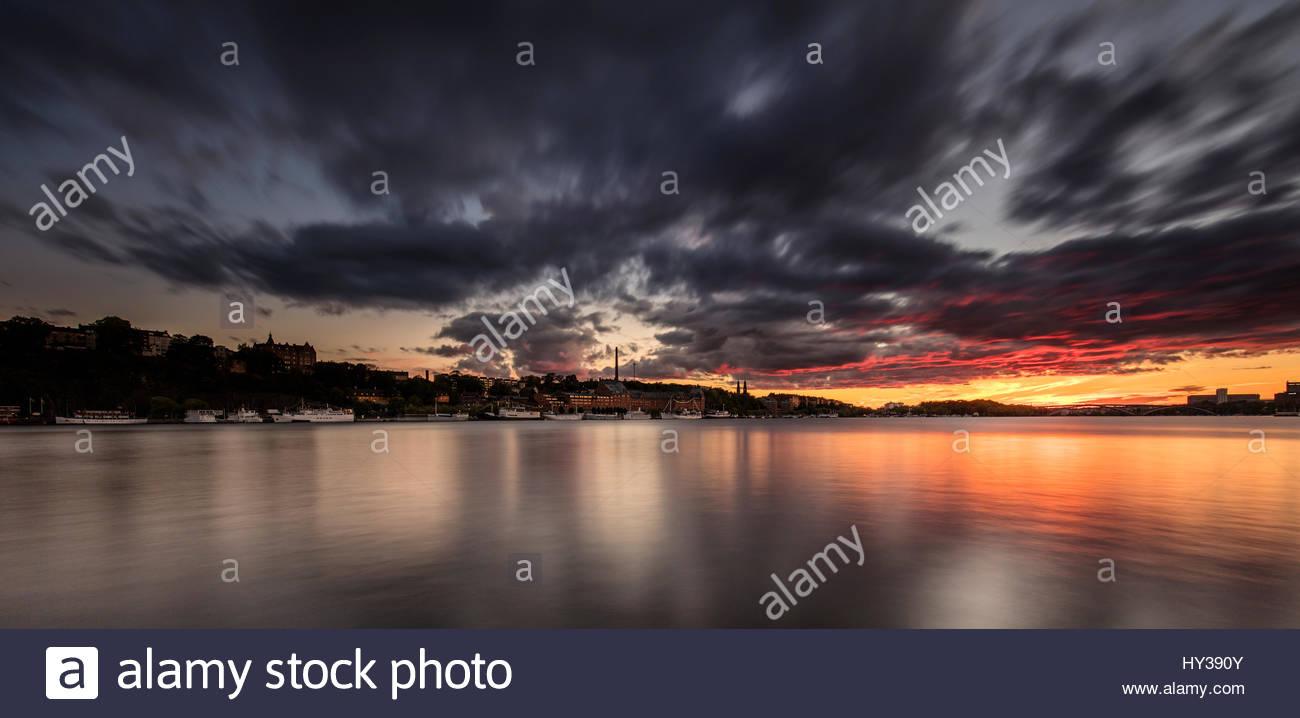 Sweden, Stockholm, Sodermalm, Dark clouds over harbor at dawn - Stock Image