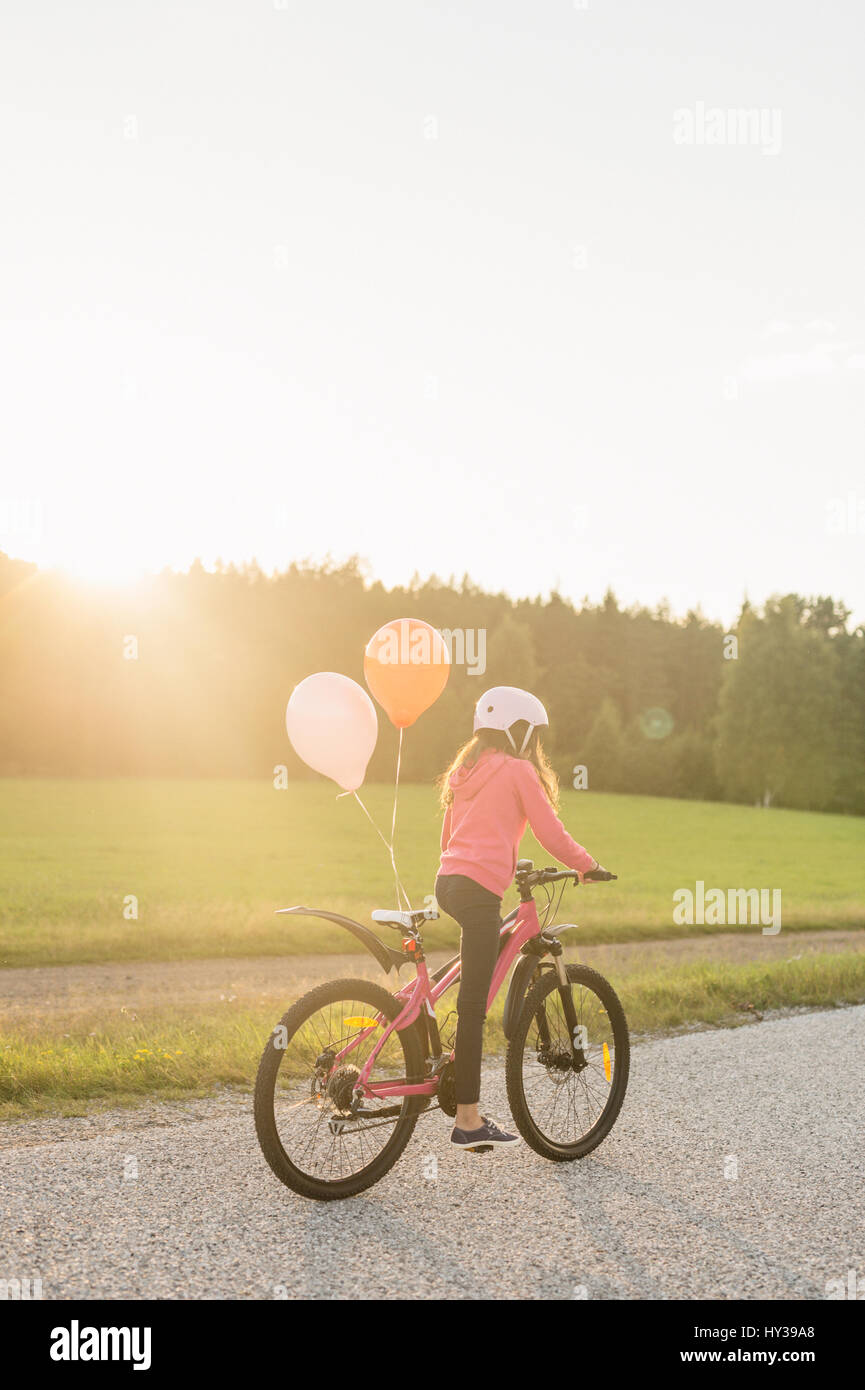 Sweden, Vastmanland, Hallefors, Bergslagen, Girl (10-11) riding bicycle at sunset - Stock Image