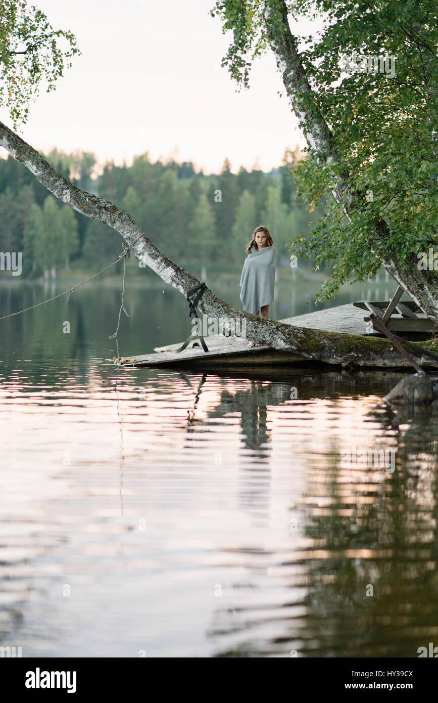 Sweden, Vastmanland, Hallefors, Bergslagen, Girl ( 8-9) standing on lakeshore - Stock Image