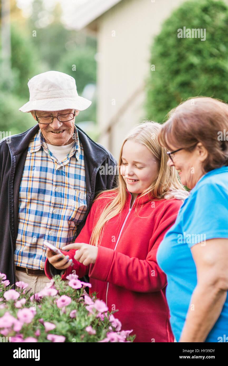 Sweden, Vastmanland, Hallefors, Bergslagen, Girl (12-13) with grandparents looking at phone - Stock Image