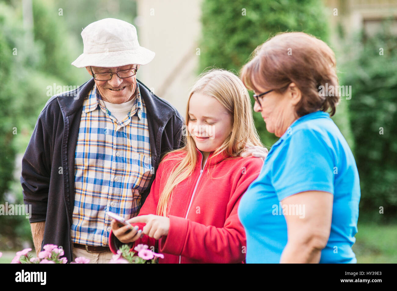 Sweden, Vastmanland, Hallefors, Bergslagen, Girl (12-13) with grandparents looking at phone display - Stock Image