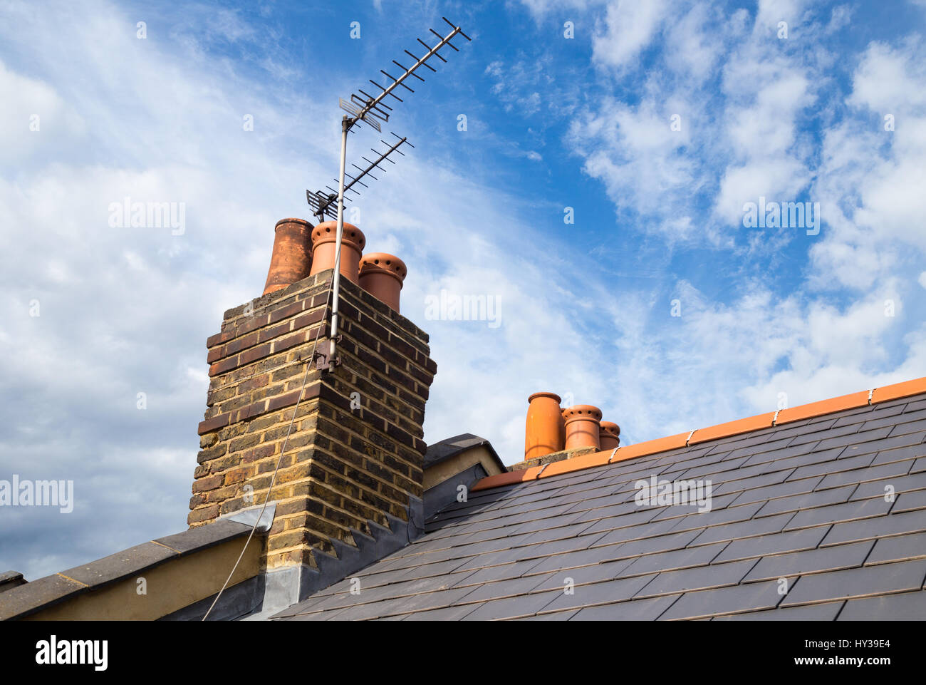 tiled roof, chimney and TV aerial of Victorian terrace house in north London - Stock Image