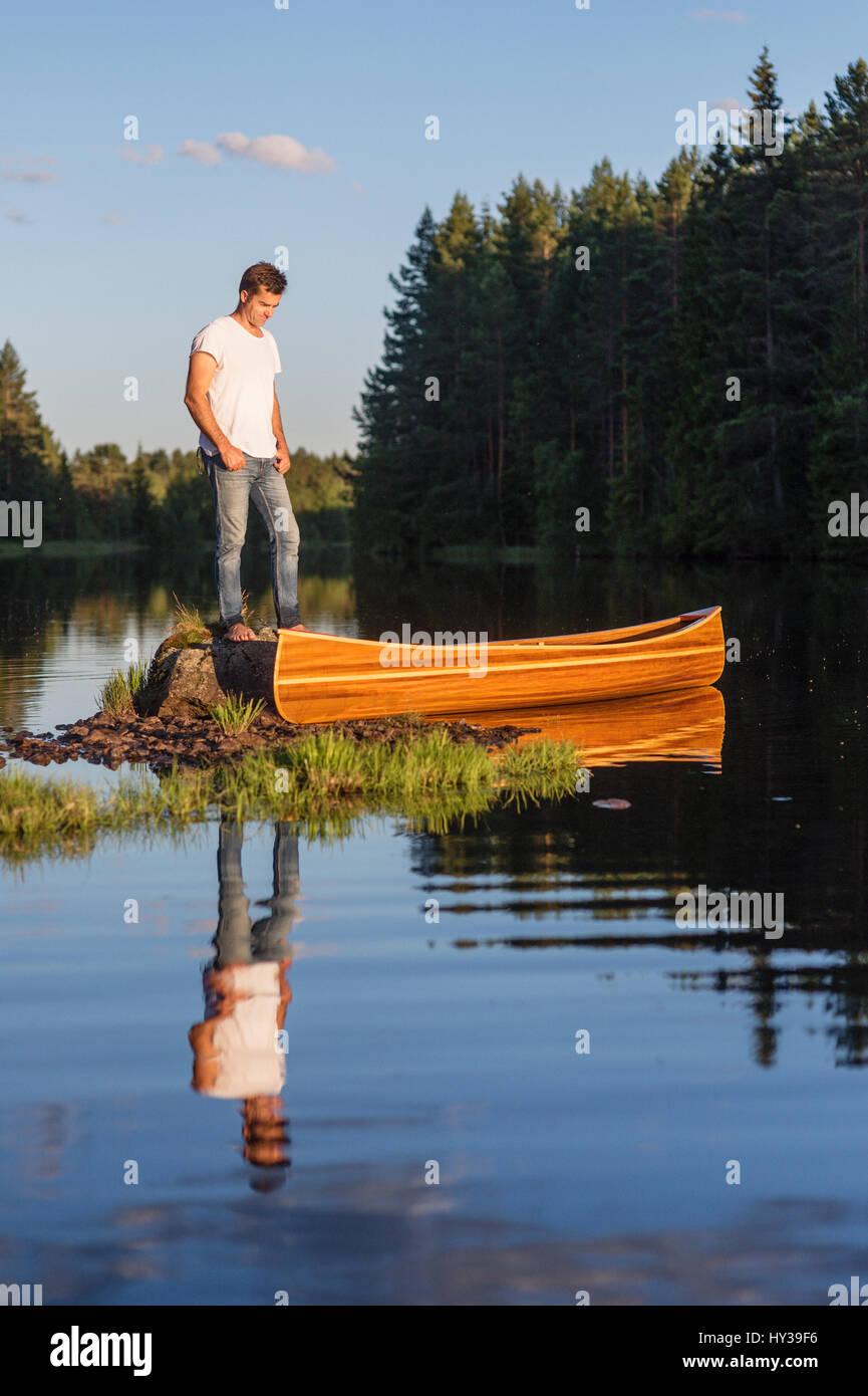 Sweden, Vastmanland, Hallefors, Bergslagen, Man standing on boulder in middle of lake Stock Photo