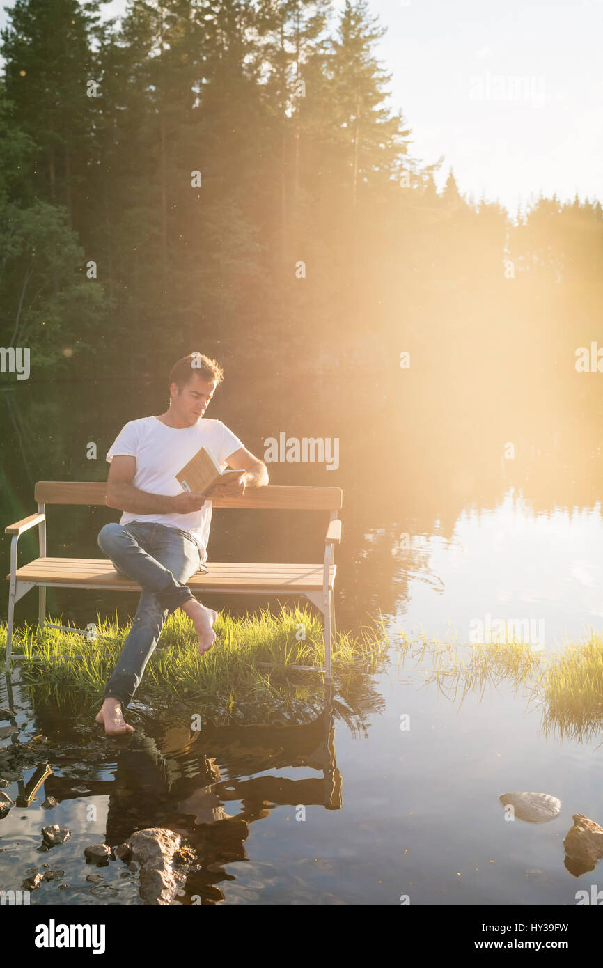 Sweden, Vastmanland, Hallefors, Bergslagen, Man sitting on bench in middle of lake - Stock Image