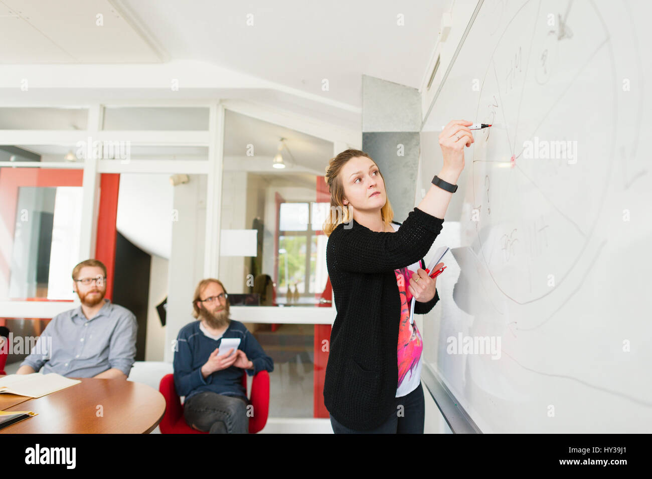 Sweden, Young woman drawing on white board during work meeting - Stock Image