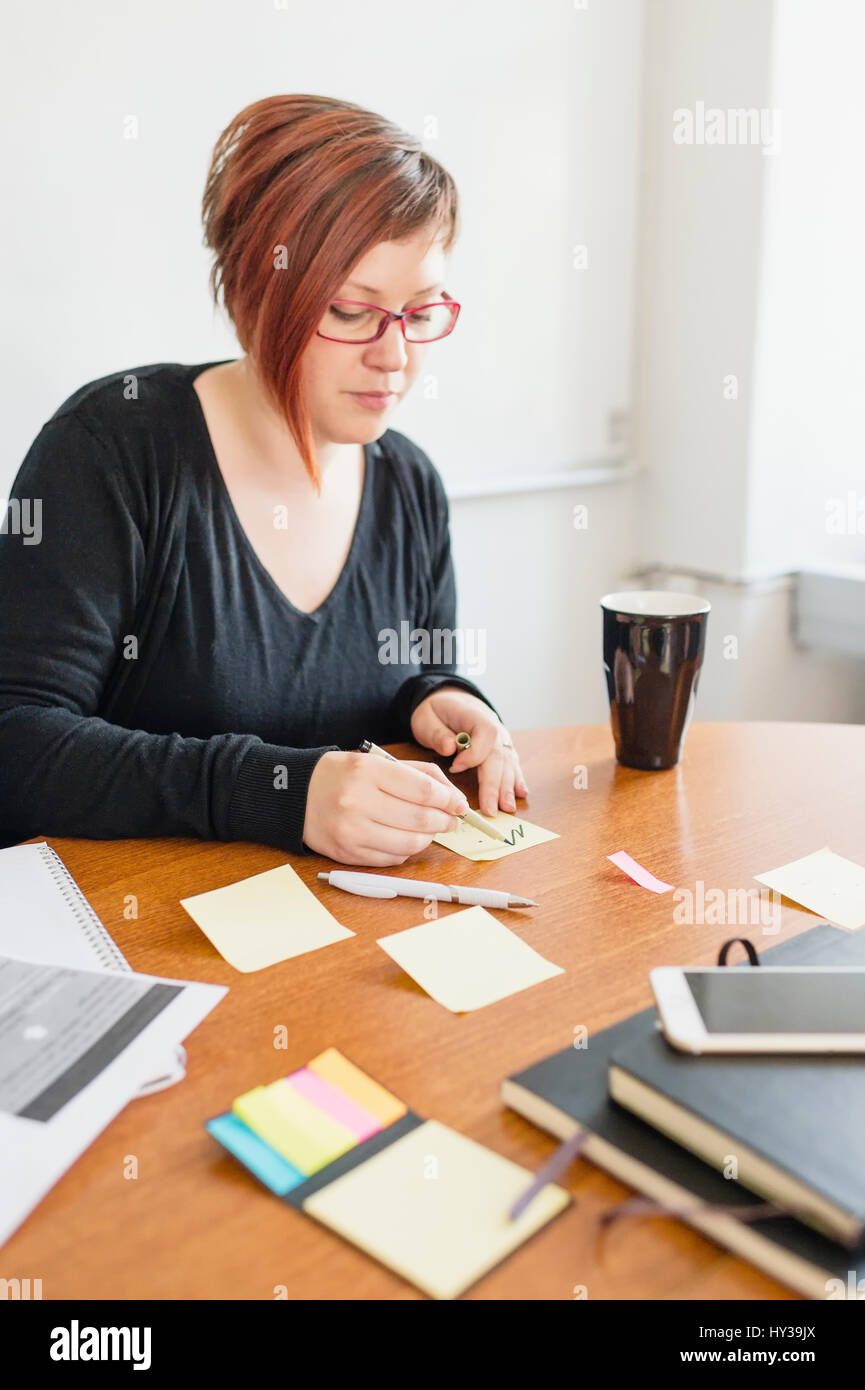Sweden, Woman making notes during work meeting - Stock Image
