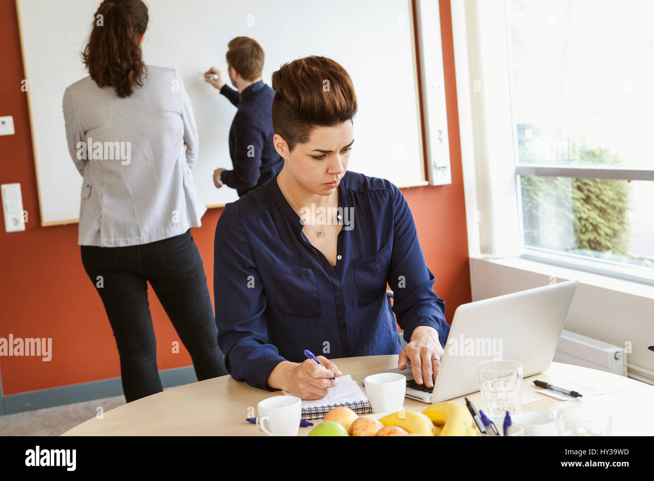 Sweden, Woman making notes during board meeting - Stock Image