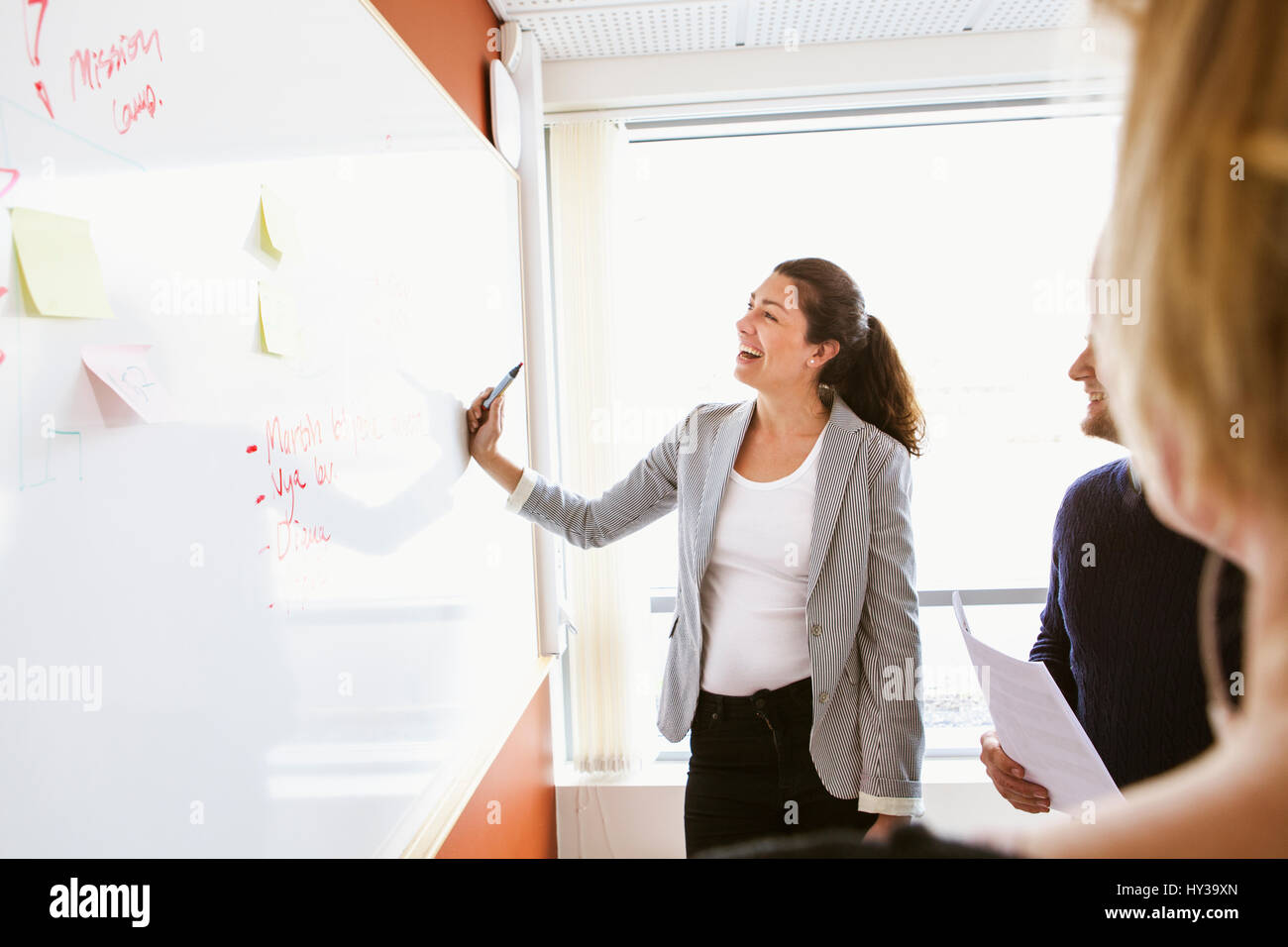 Sweden, Businesswoman standing at board and laughing during business meeting - Stock Image
