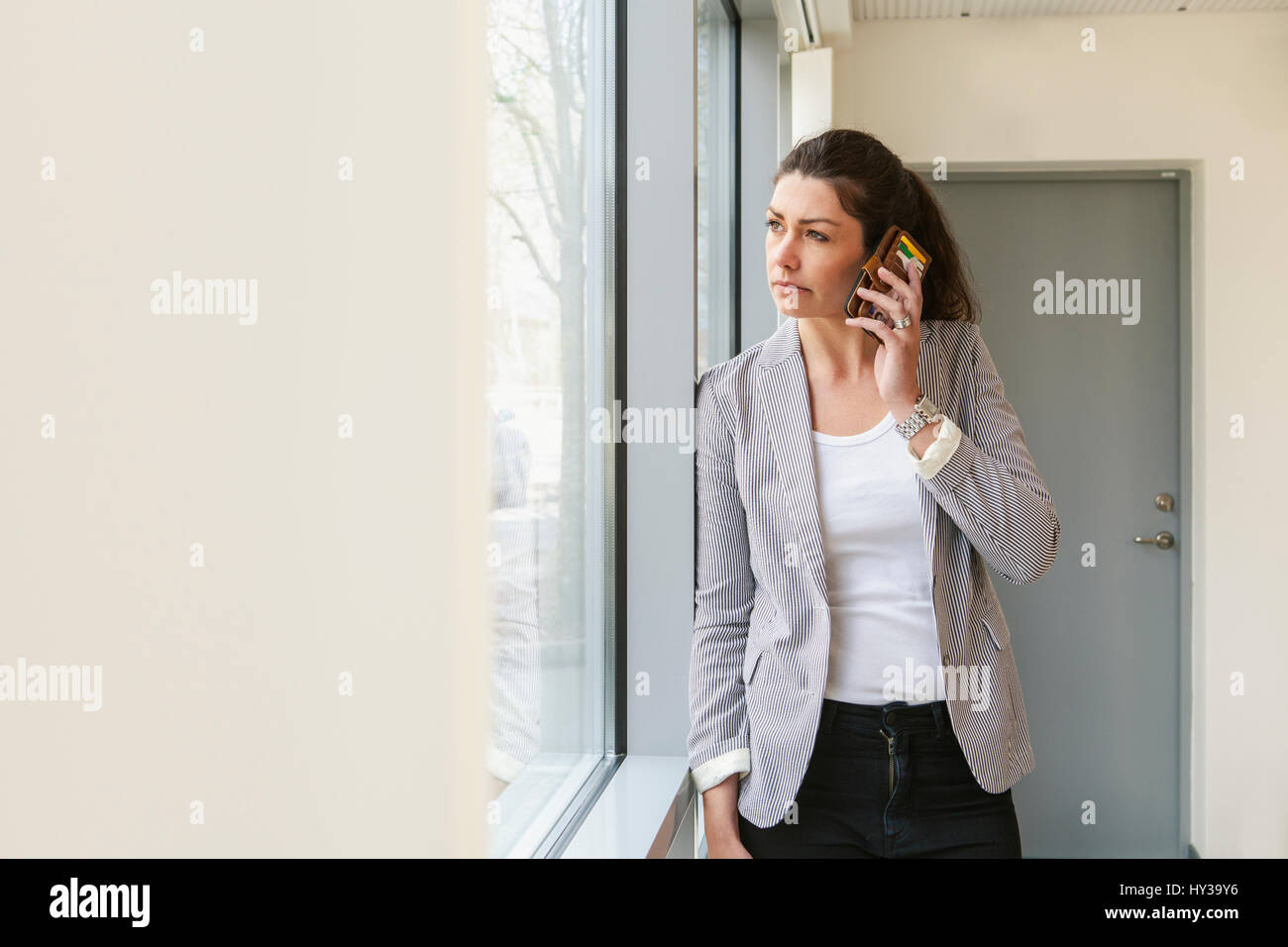 Sweden, Businesswoman looking through window and using smartphone - Stock Image