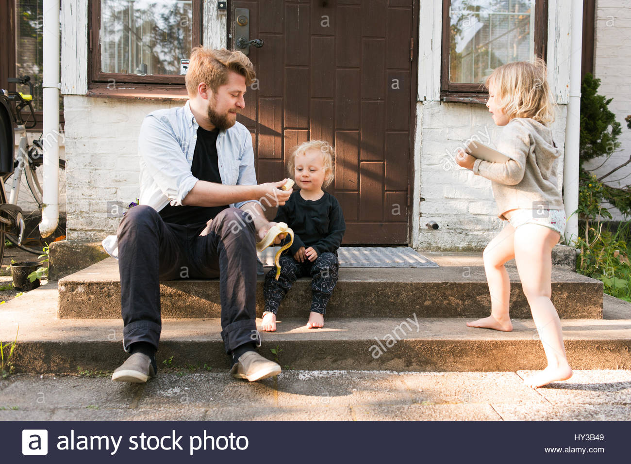 Sweden, Skane Father sitting on steps and feeding son (2-3) - Stock Image
