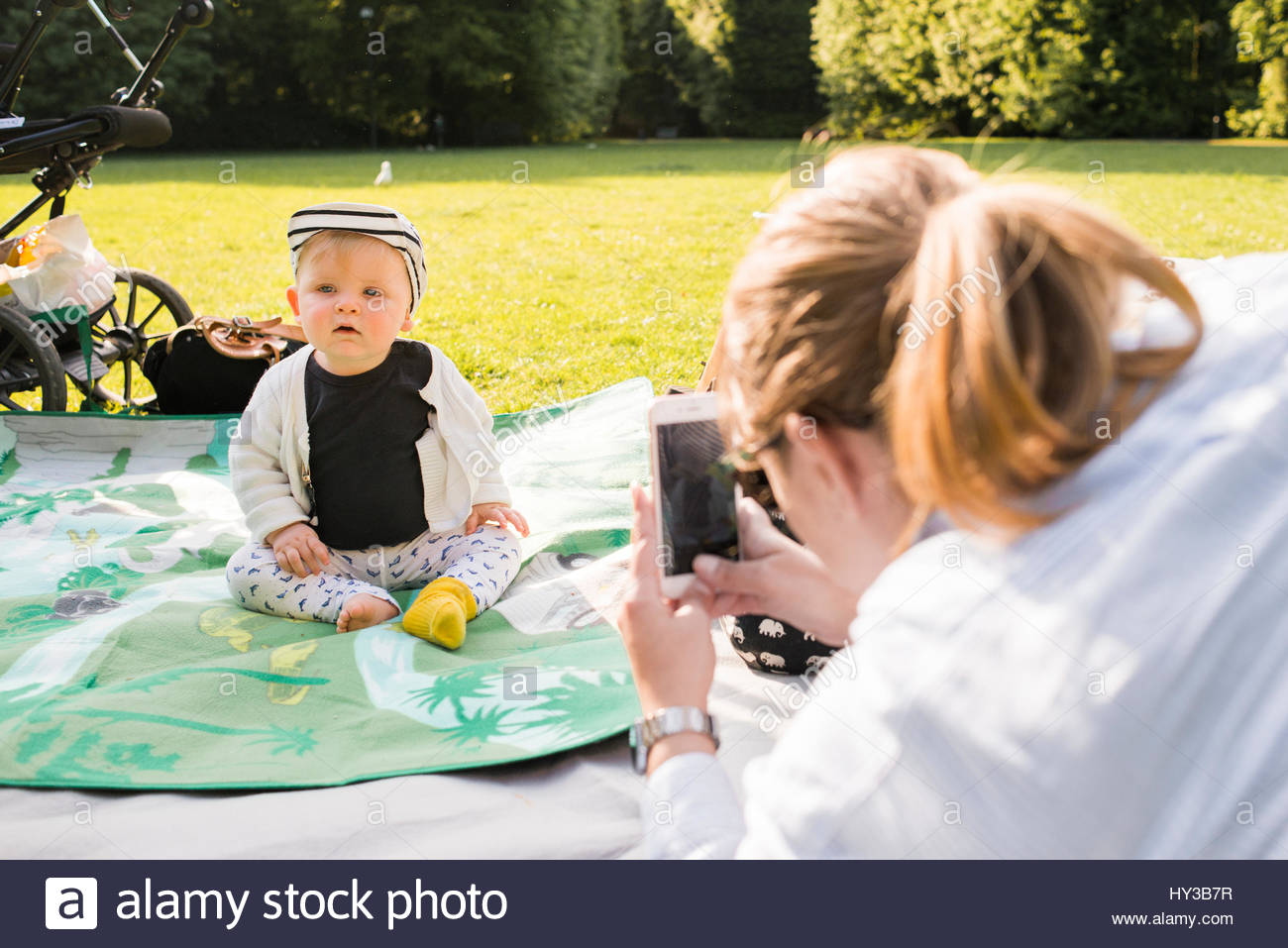 Sweden, Skane, Malmo, Mother photographing son (18-23 months) in park - Stock Image