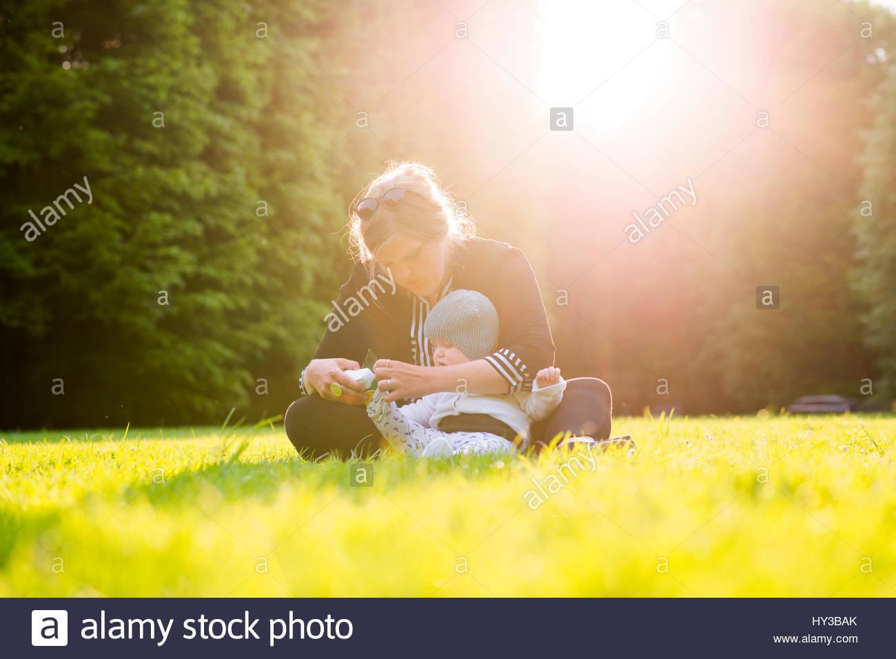 Sweden, Skane, Malmo, Mother dressing son (18-23 months) in park - Stock Image