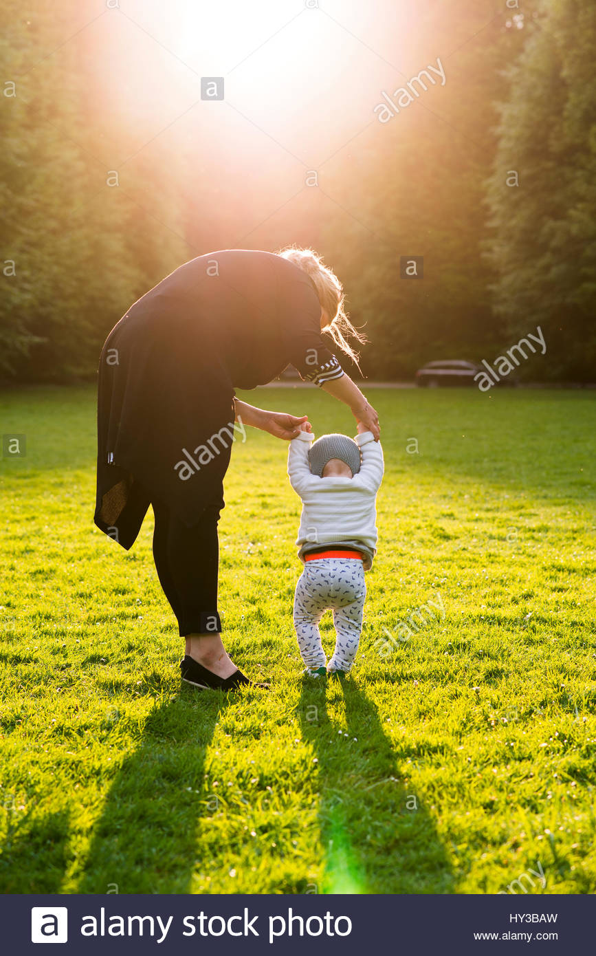 Sweden, Skane, Malmo, Mother walking with son (18-23 months) in park - Stock Image