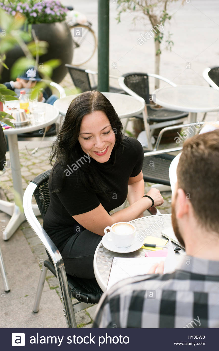 Sweden, Skane, Malmo, People talking at sidewalk cafe - Stock Image