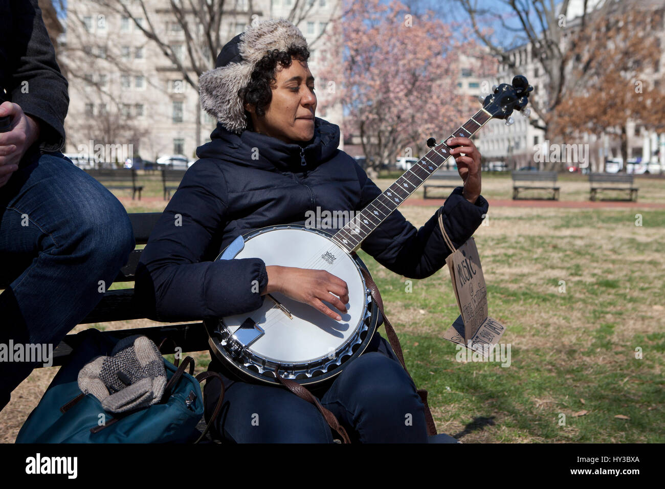 African-American woman playing banjo in a public park  USA - Stock Image