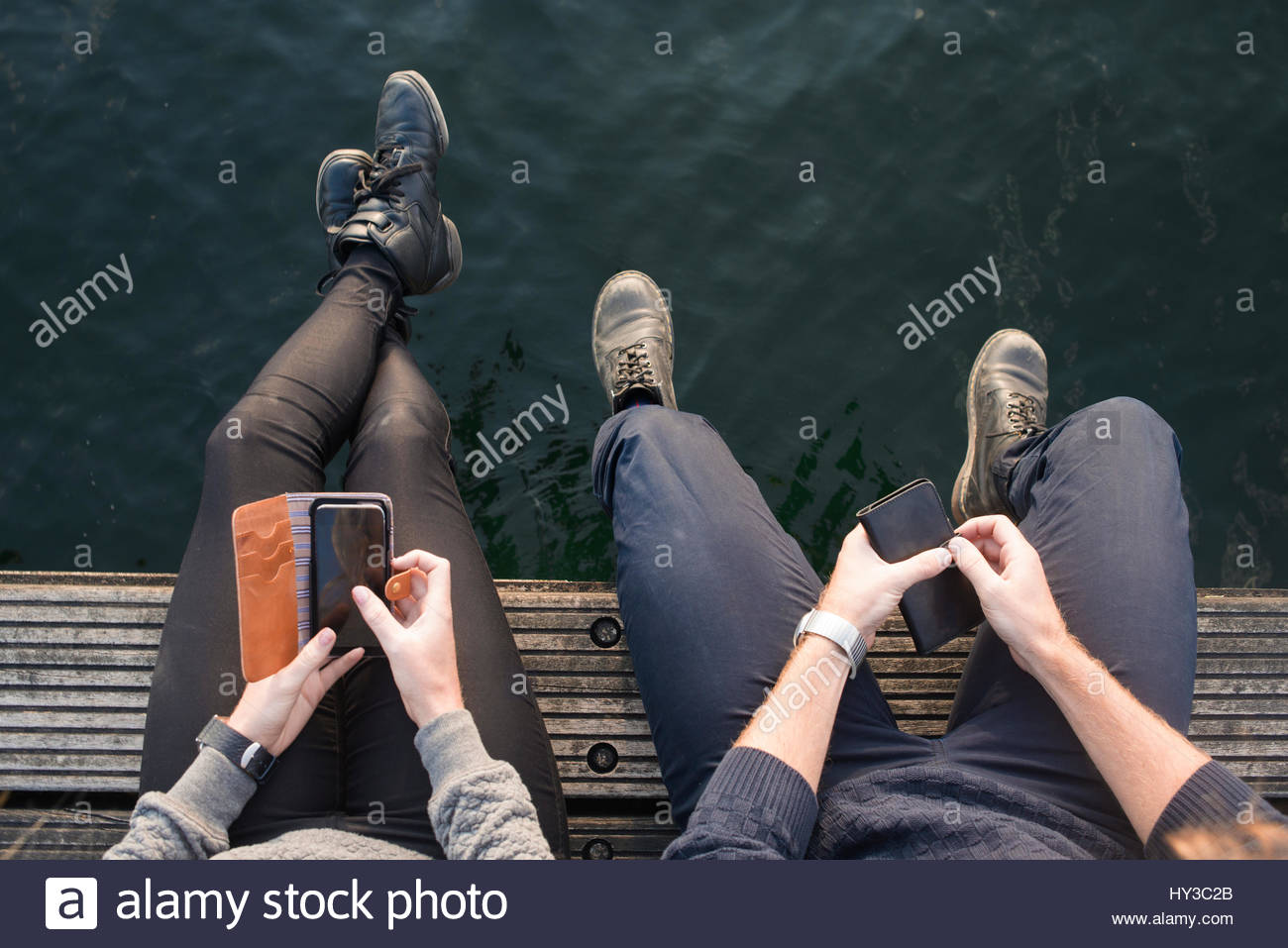 Sweden, Skane, Malmo, Overhead view of young man and woman sitting on pier with smart phones - Stock Image