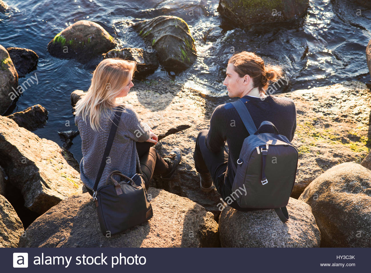 Sweden, Skane, Malmo, Young man and woman talking on rocky seashore - Stock Image