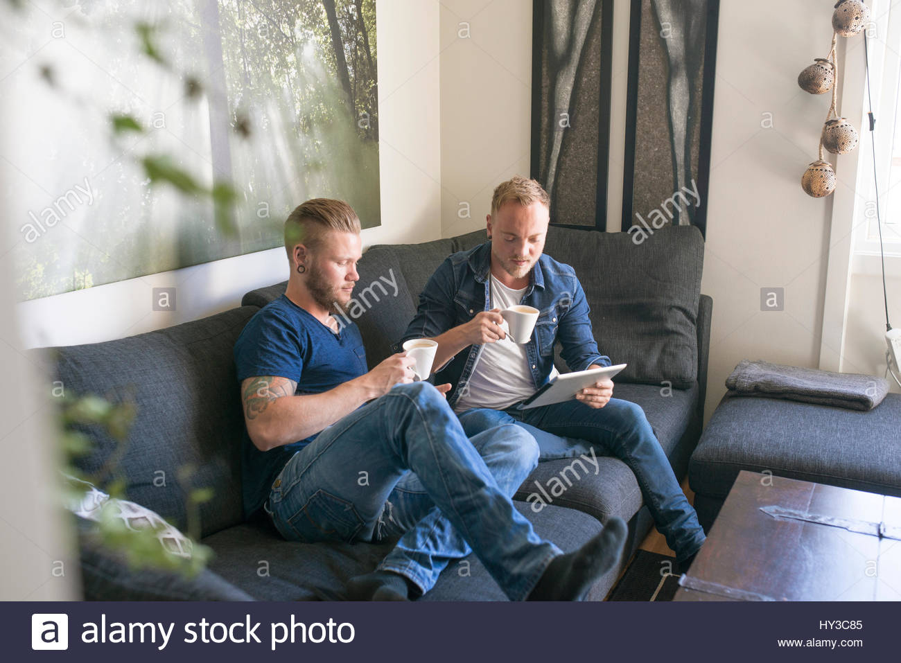 Norway, Couple using tablet and drinking coffee on sofa - Stock Image