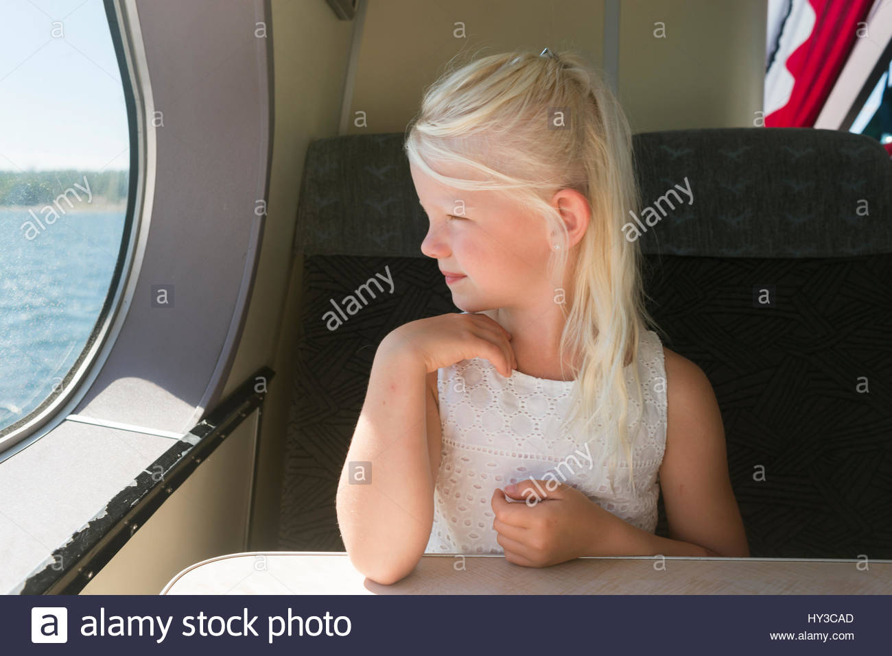 Sweden, Girl (6-7) looking through window on ship - Stock Image