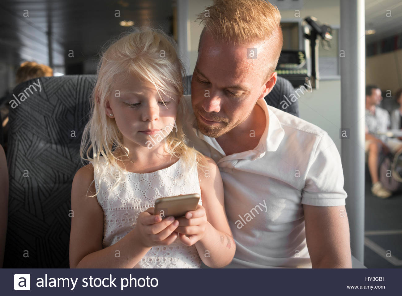 Sweden, Girl (6-7) and father using cell phone in ship cabin - Stock Image