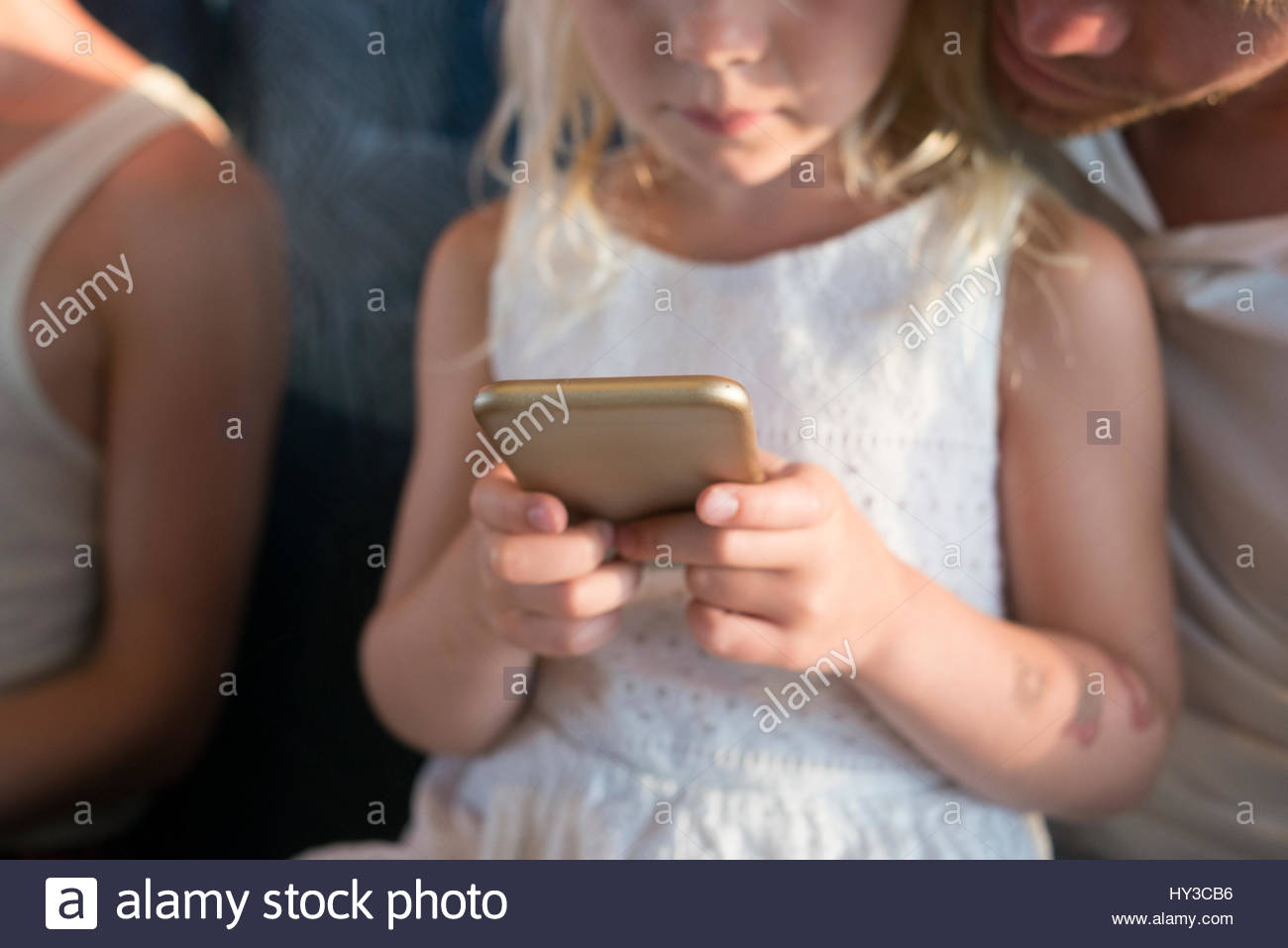 Sweden, Girl (6-7) and father using cell phone - Stock Image