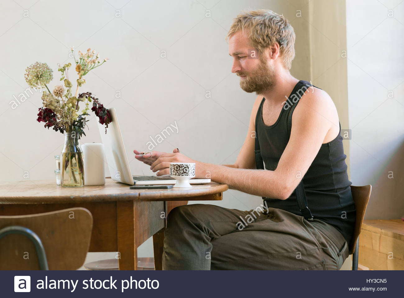 Sweden, Man using laptop and smart phone - Stock Image