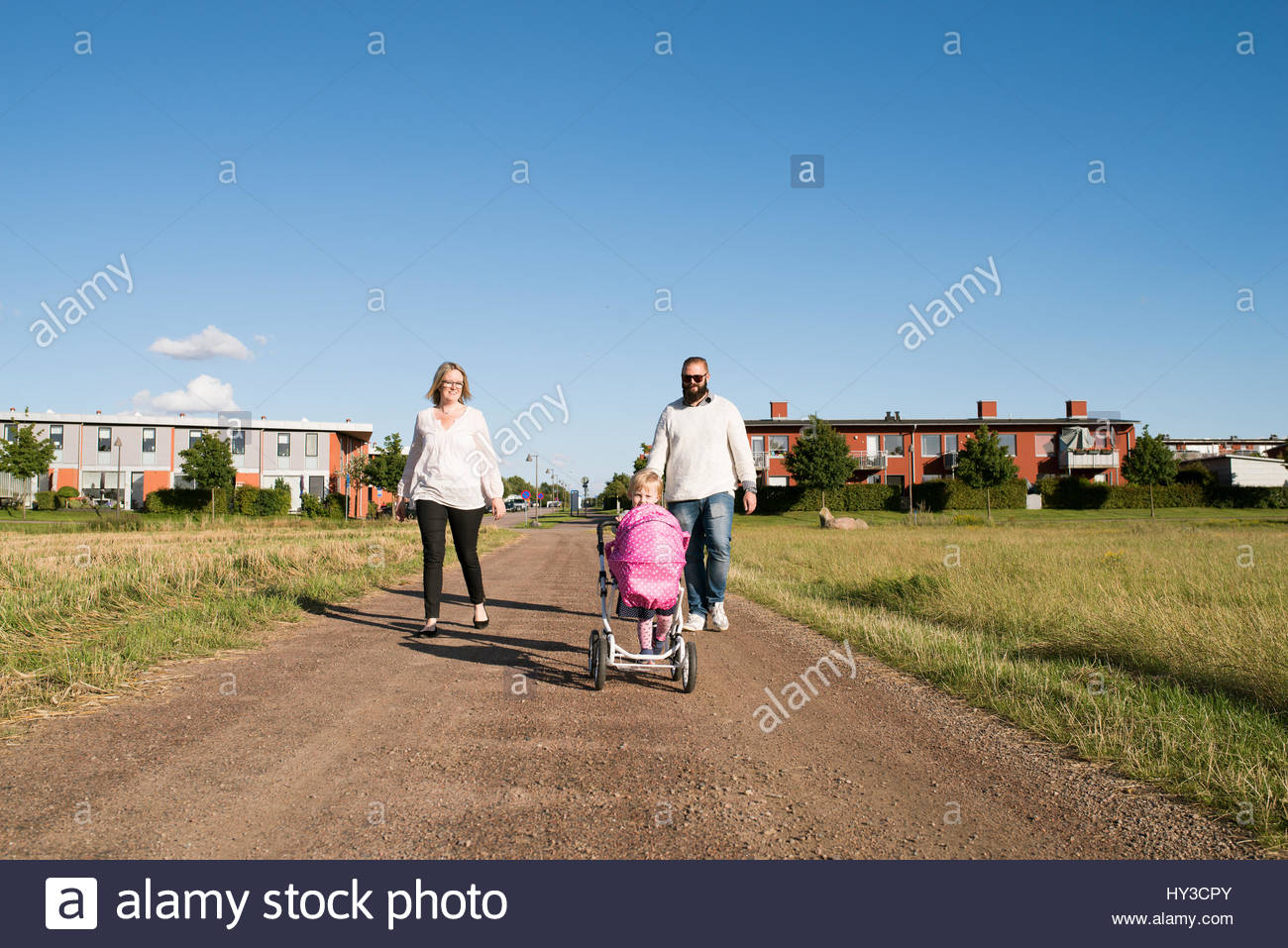 Sweden, Parents and daughter (2-3) walking in rural setting - Stock Image