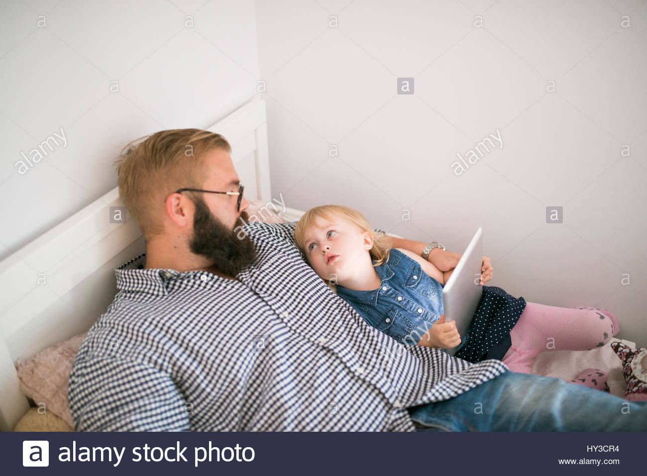 Sweden, Father lying in bed with daughter (2-3) - Stock Image