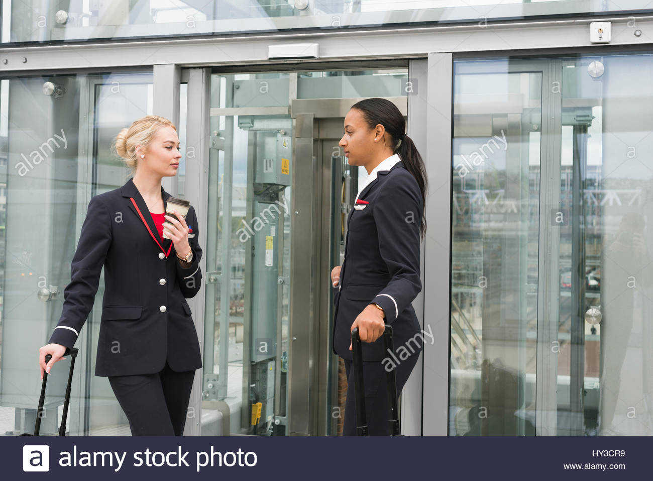 Norway, Oslo, Stewardesses standing with suitcases - Stock Image