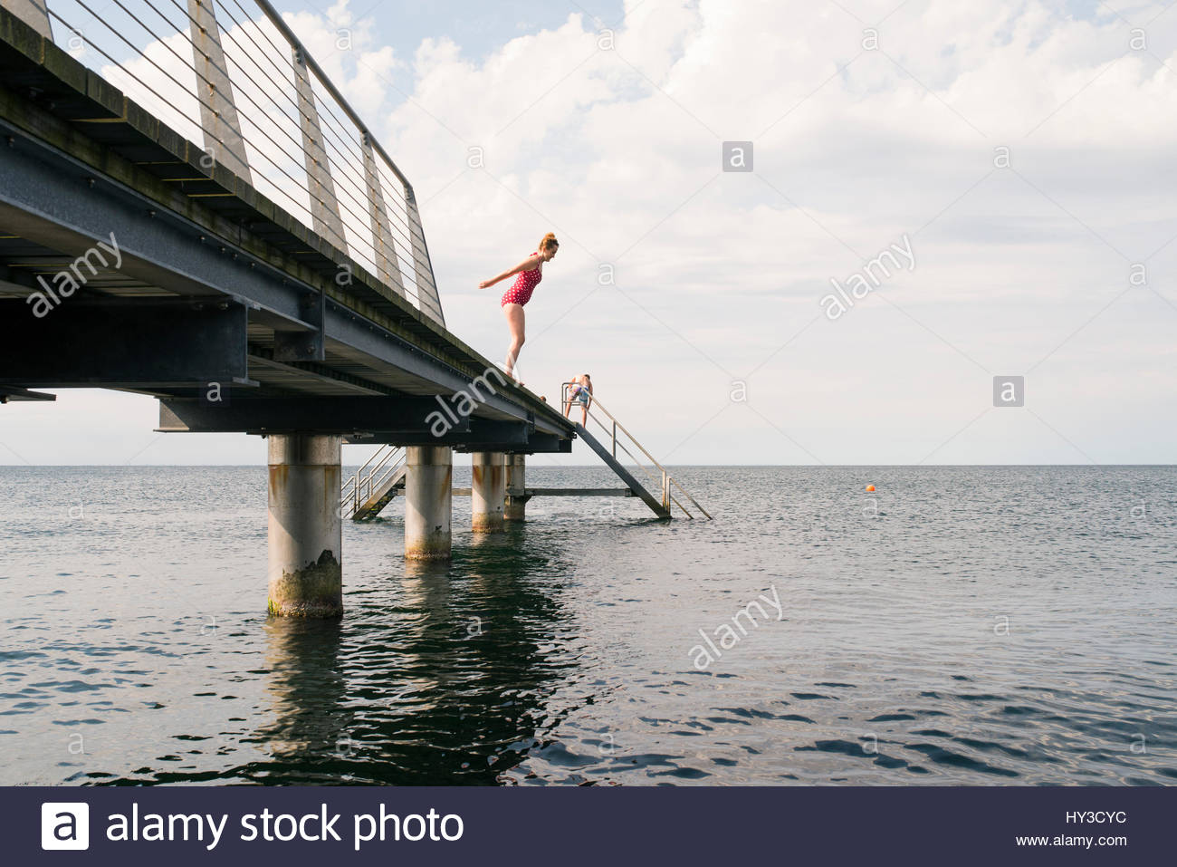 Sweden, Skane, Malmo, Woman jumping into water from pier - Stock Image