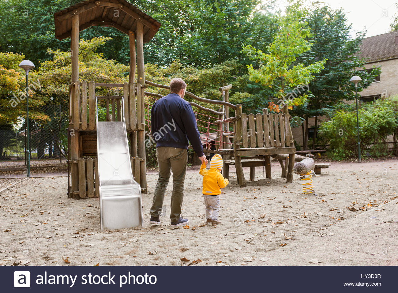 Sweden, Skane, Malmo, Father walking with son ( 12-17 months) next to slide in playground - Stock Image