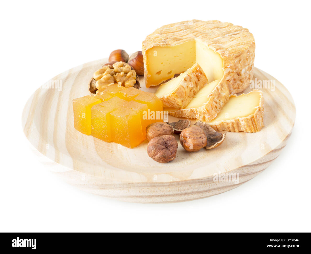 Soft washed-rind cheese, hazelnuts, walnut and marmalade on the textured wooden board isolated on white - Stock Image