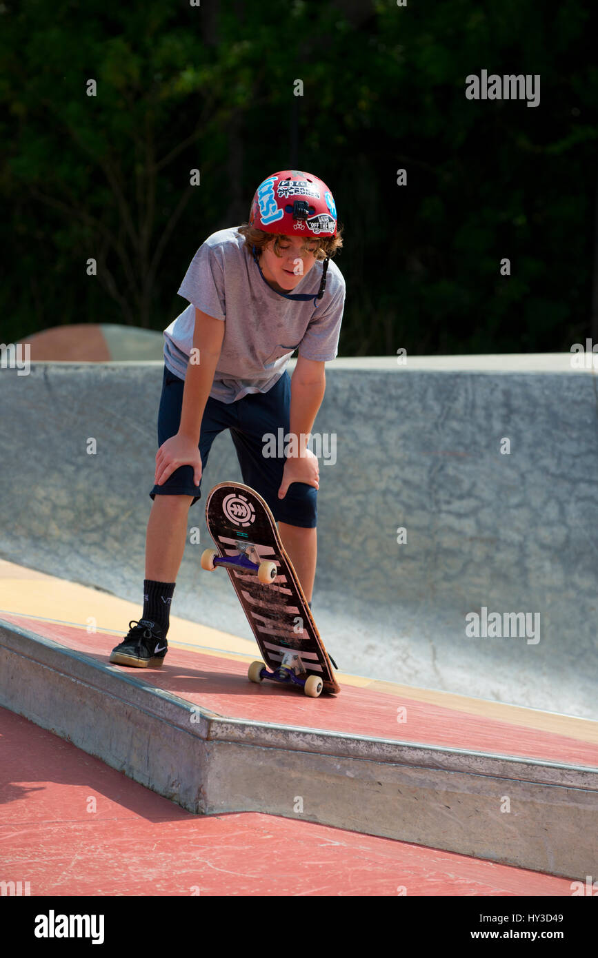 young boy on skate board looking on - Stock Image