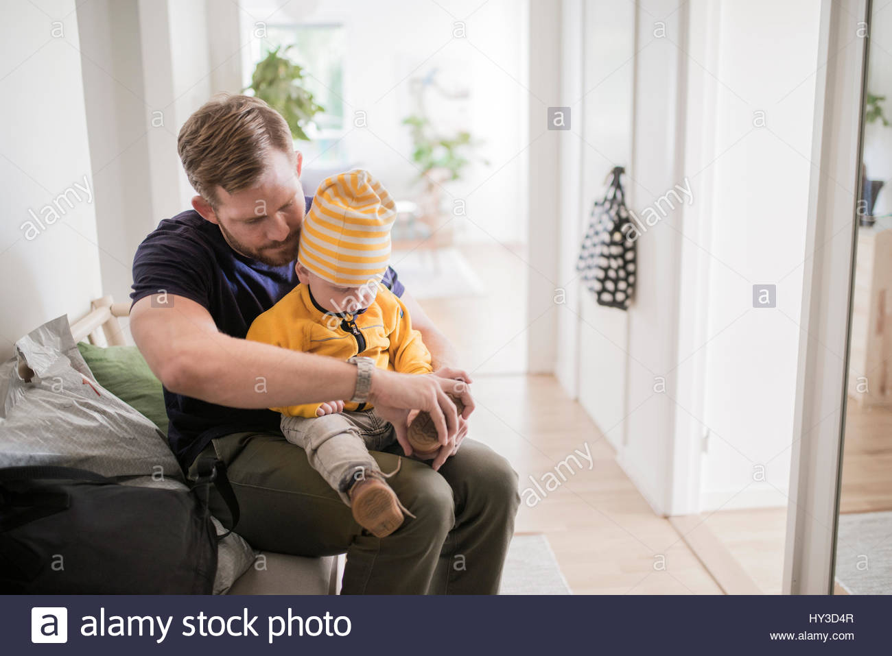 Sweden, Father sitting and undressing son (12-17 months) - Stock Image
