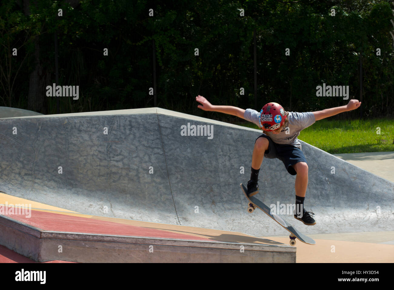 young boy on skate board jumping - Stock Image