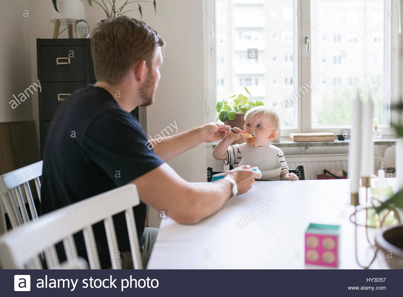 Sweden, Father helping son (12-17 months) eating at table - Stock Image