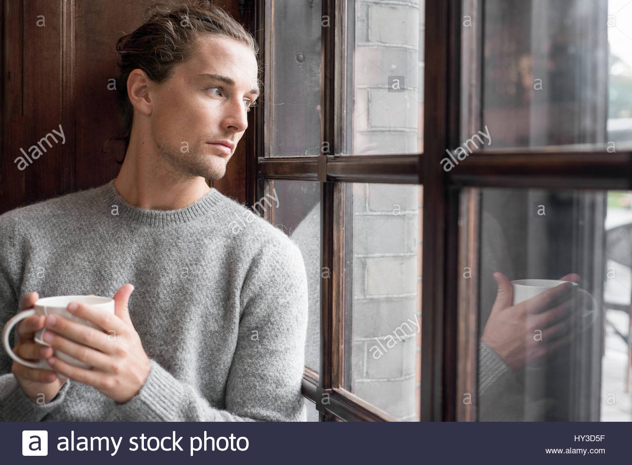 Sweden, Man holding mug and looking through window - Stock Image