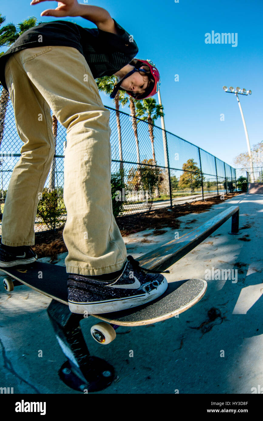 young boy on skate board riding  pipe - Stock Image