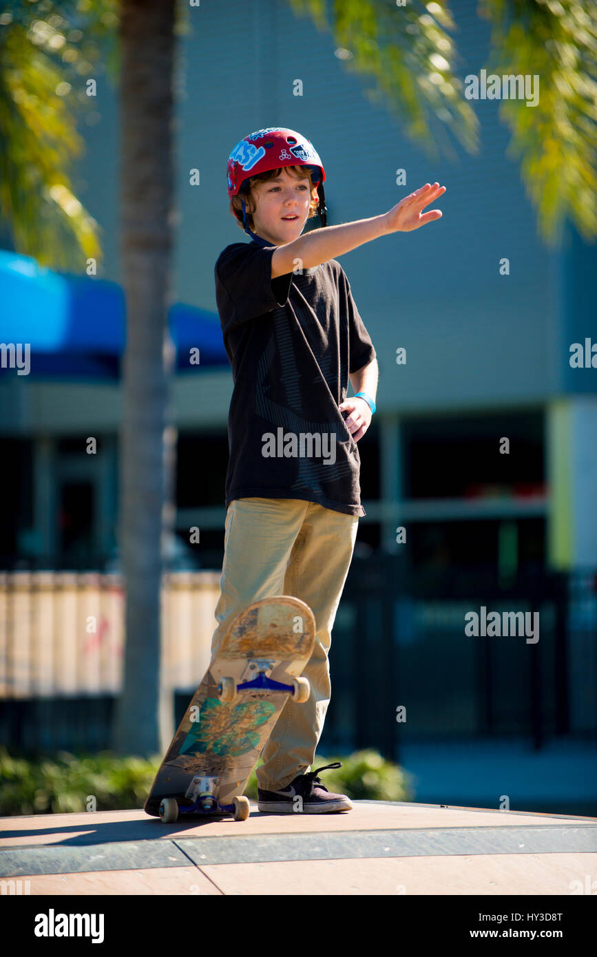 young boy on skate board showing way - Stock Image