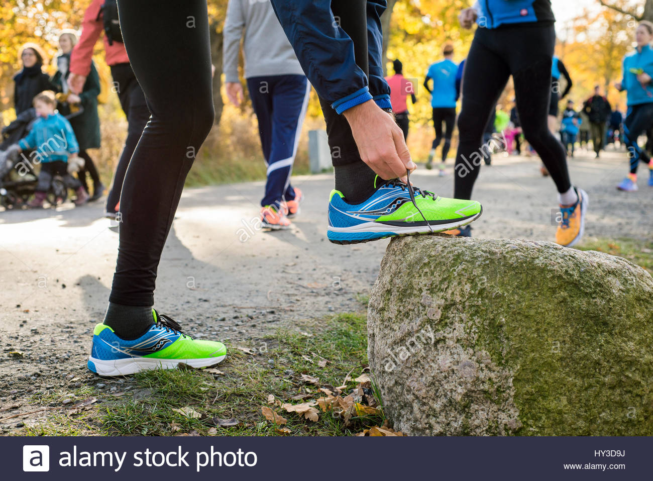 Sweden, Man tying shoe in park - Stock Image