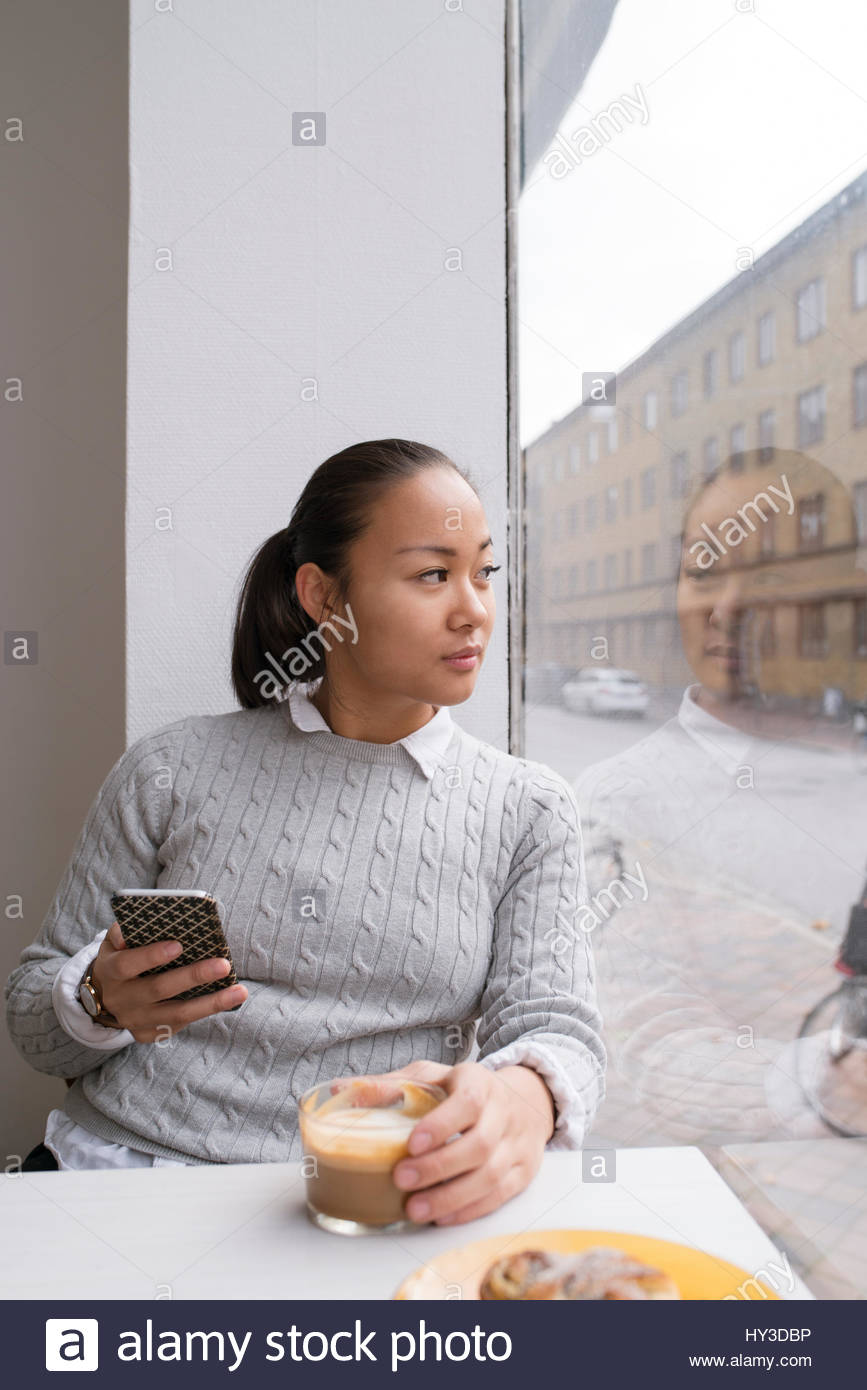 Sweden, Woman holding smart phone and looking through window - Stock Image