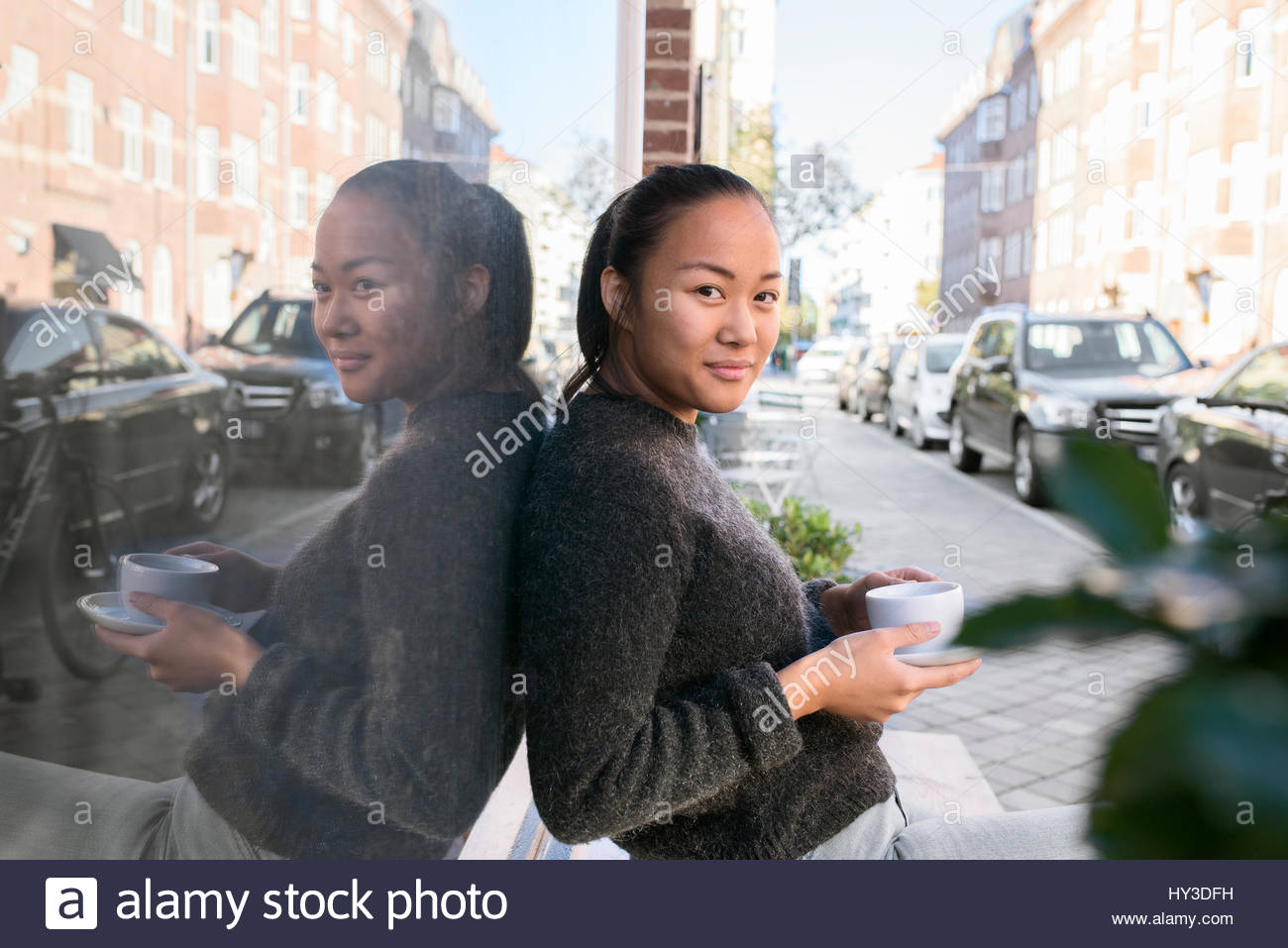 Sweden, Skane, Malmo, Woman sitting and holding cafe cup - Stock Image