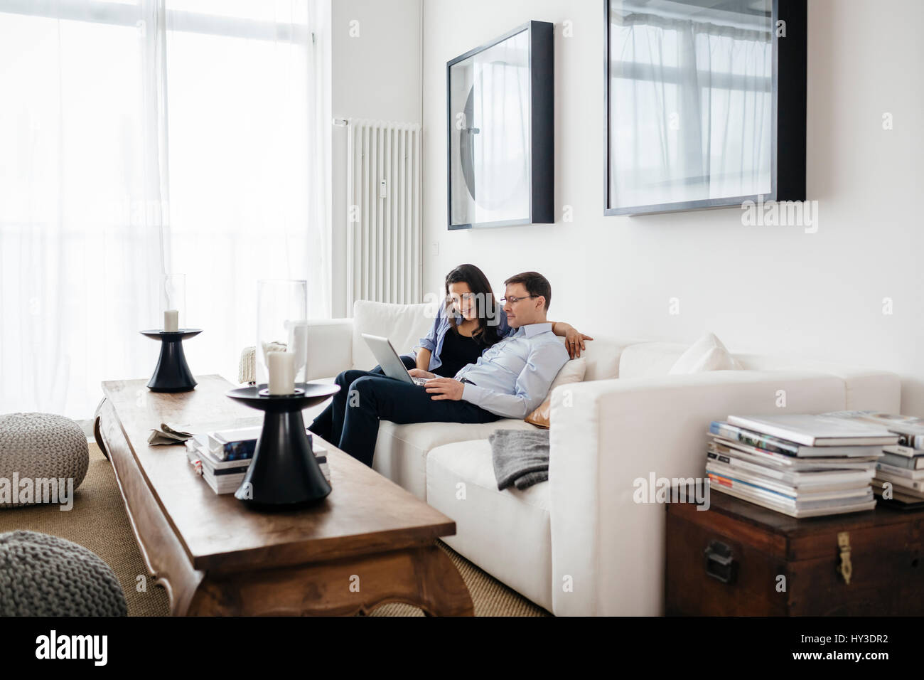 Germany, Man and woman sitting on sofa with laptop - Stock Image
