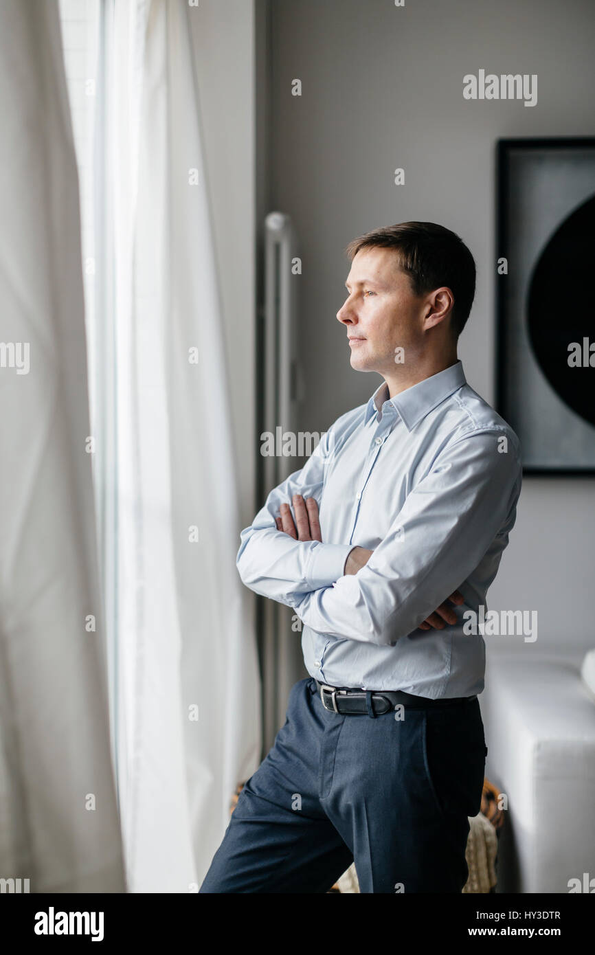 Germany, Man looking through window - Stock Image