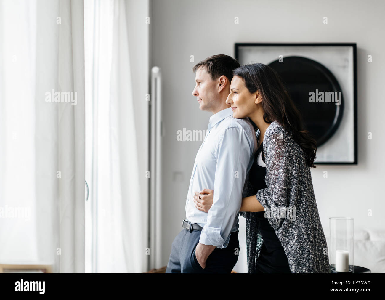 Germany, Couple hugging by window - Stock Image