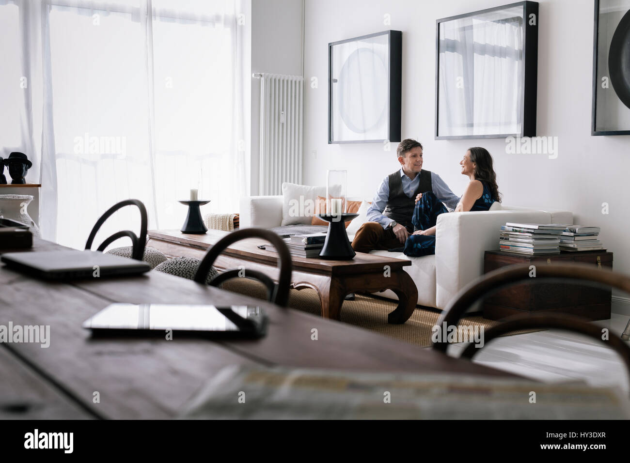 Germany, Couple sitting on sofa in living room - Stock Image
