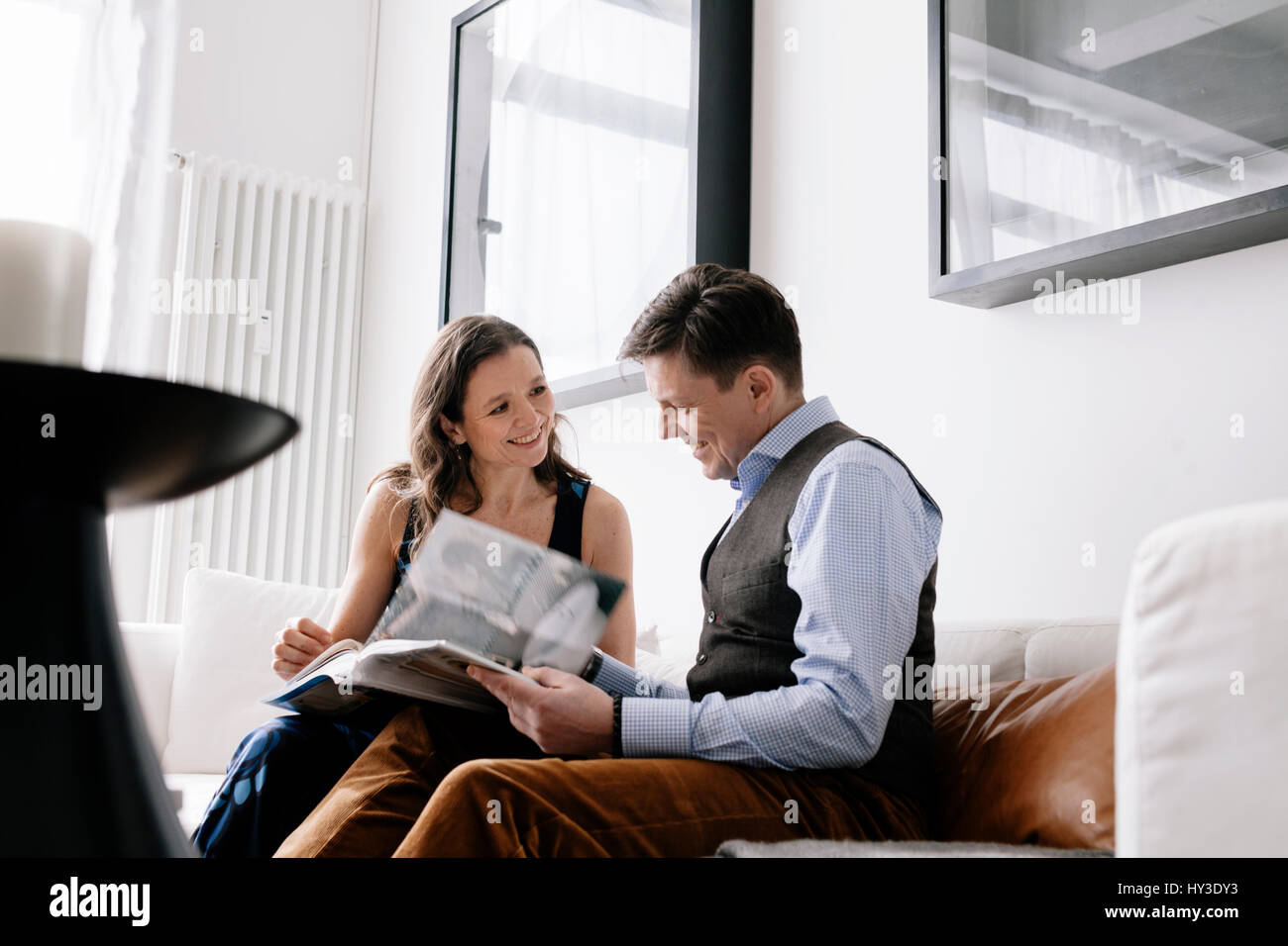 Germany, Couple sitting on sofa and reading book - Stock Image