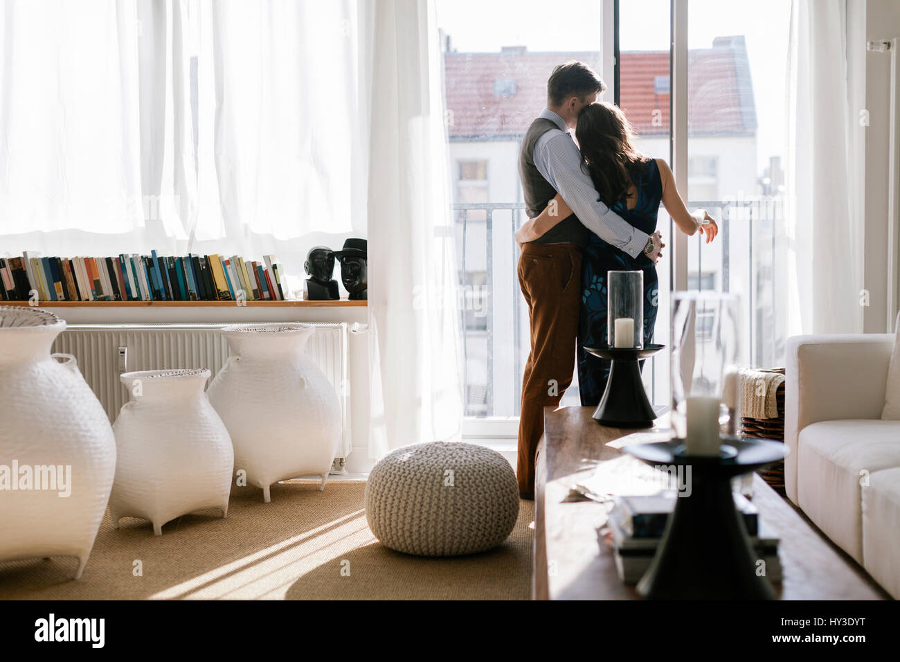 Germany, Couple hugging by window in living room - Stock Image