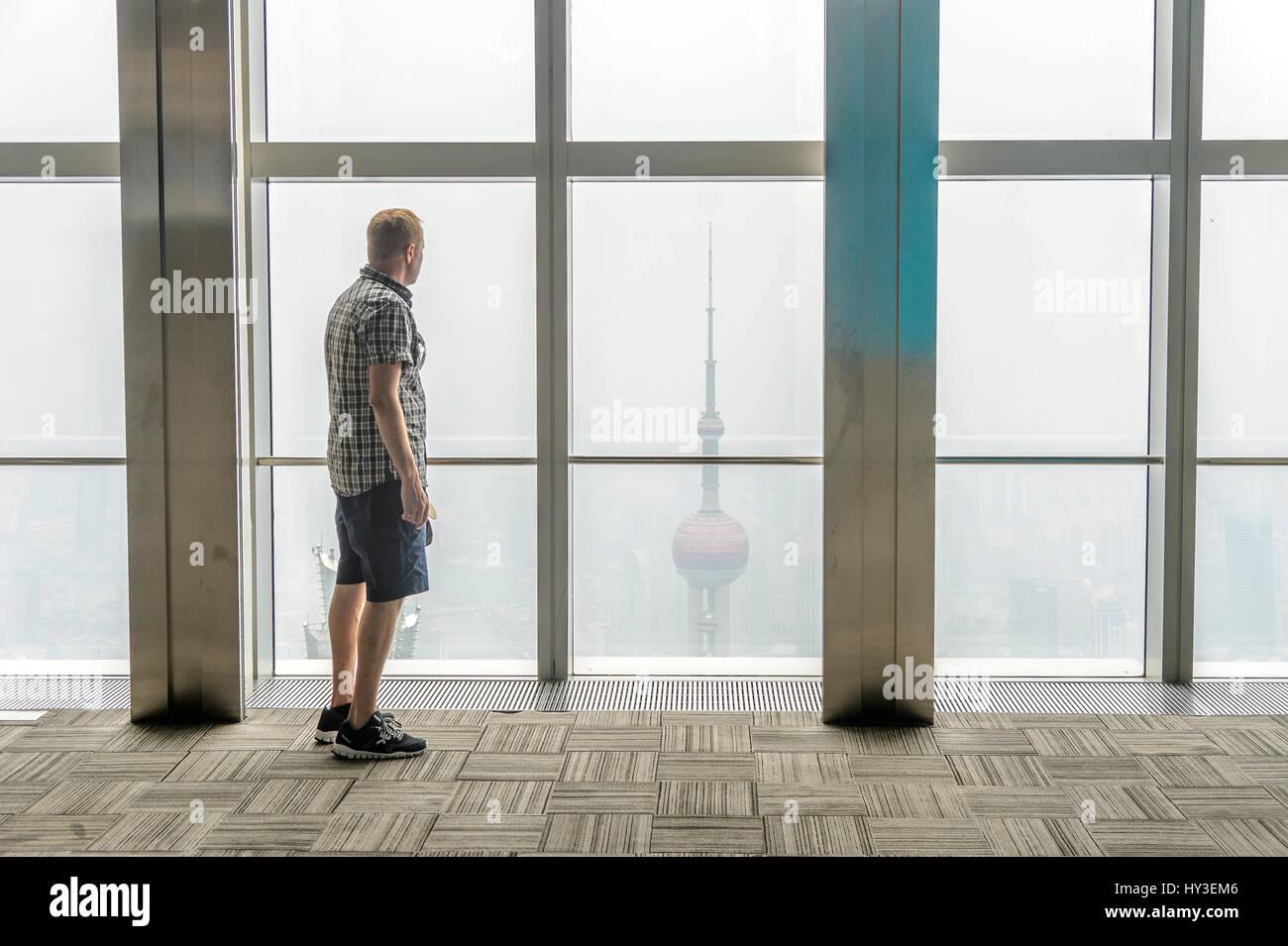 China, Shanghai, Man looking through window - Stock Image