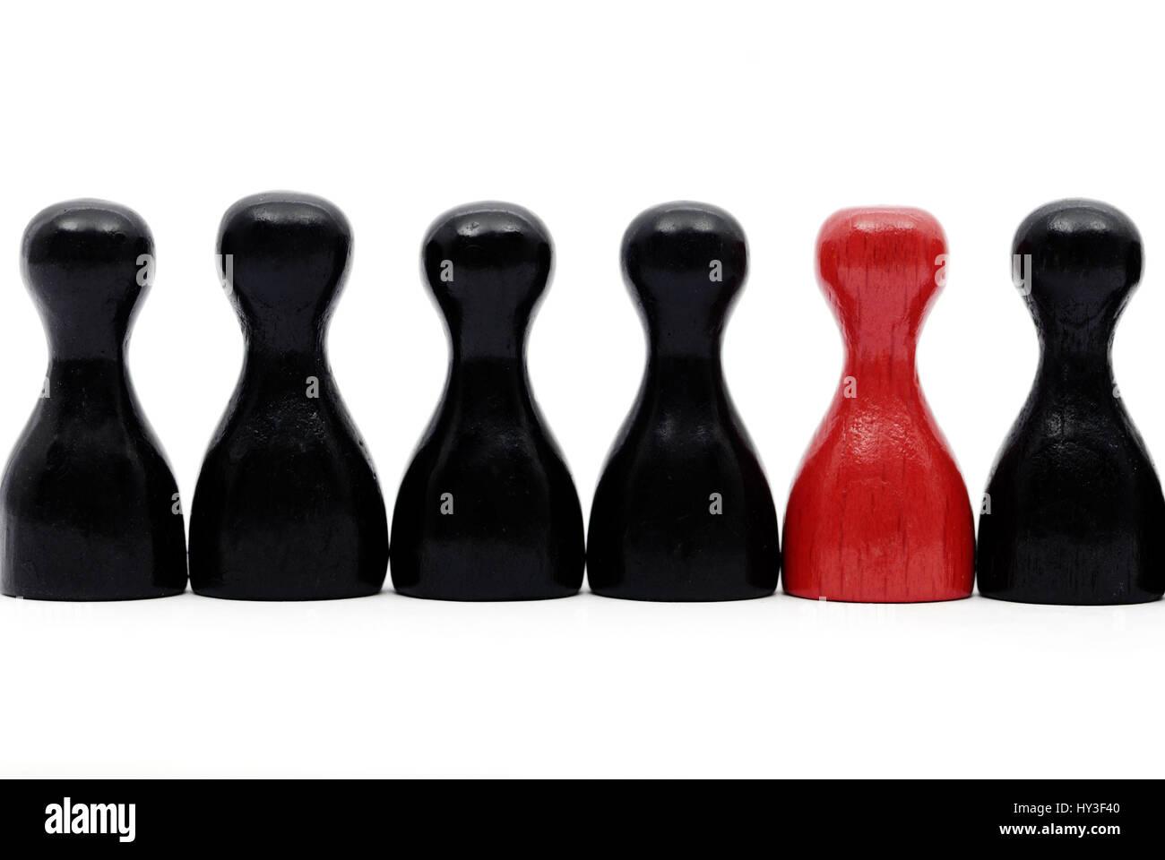 Red play figure in the midst of black play figures, Rote Spielfigur inmitten von schwarzen Spielfiguren - Stock Image